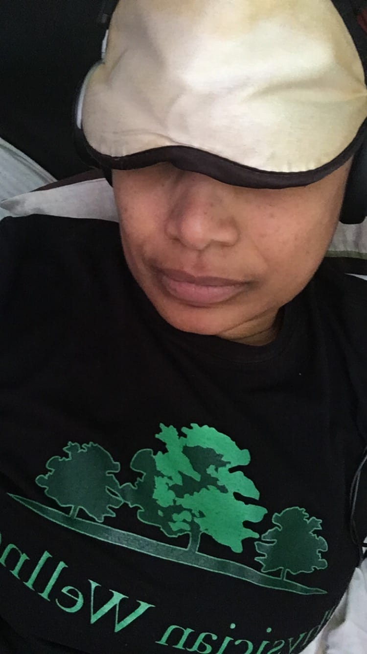 Laying in bed with a sleep mask on, wearing a black t-shirt with green writing - Physician Wellness