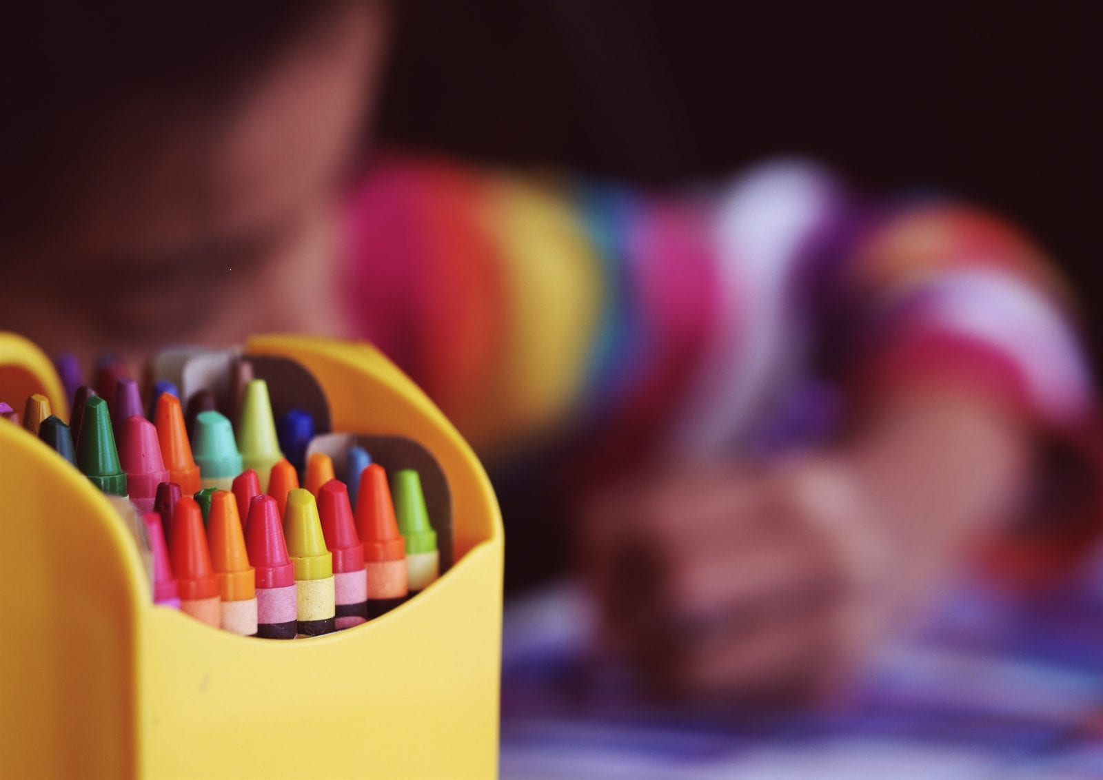 focus on a box of colored crayons, blurred child coloring in the background