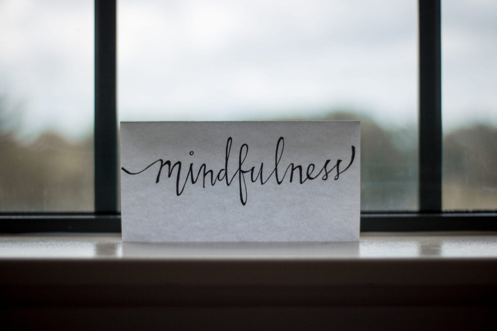 cursive writing the word mindfulness on a white placecard on the window sill